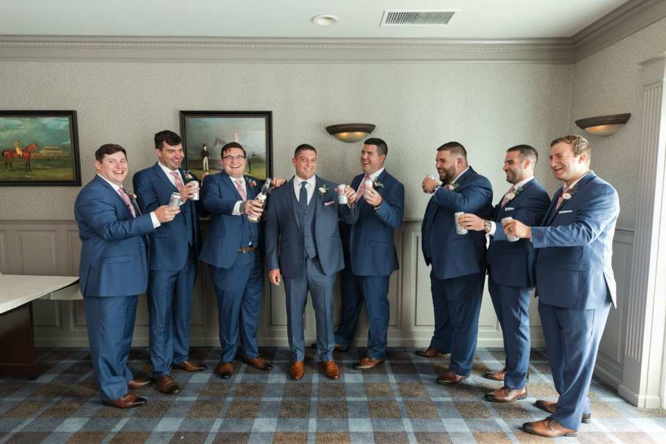 The groom and groomsmen in blue suits by Generation Tux enjoying some beer while getting ready for the wedding