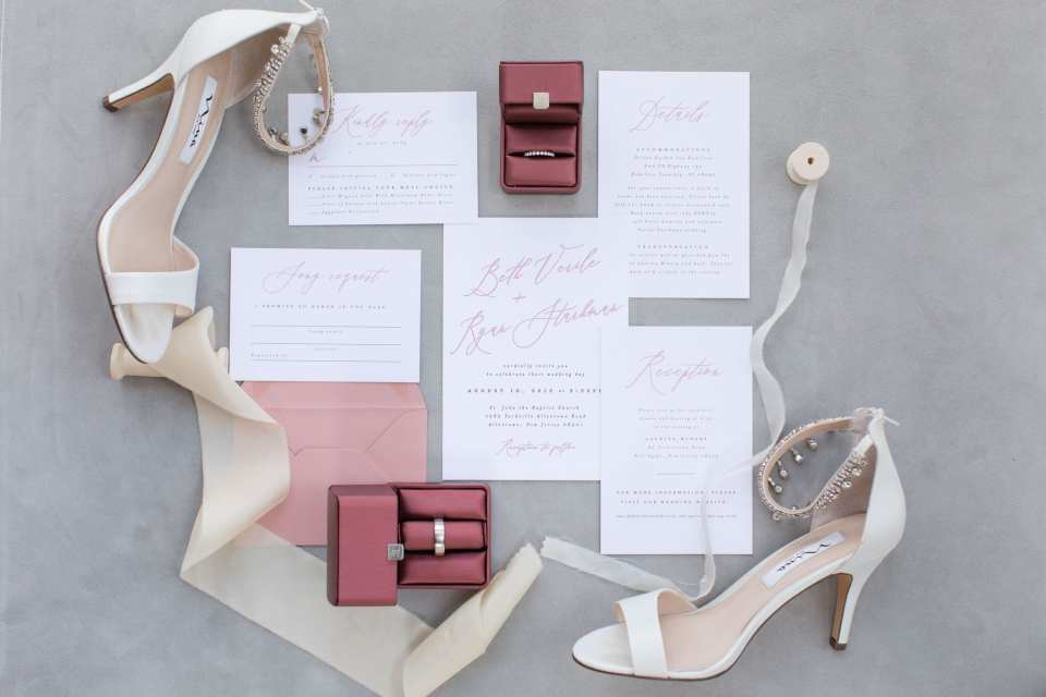 wedding details: white and pink invitation suite, burgundy ring boxes with wedding rings inside and the brides shoes by Nina