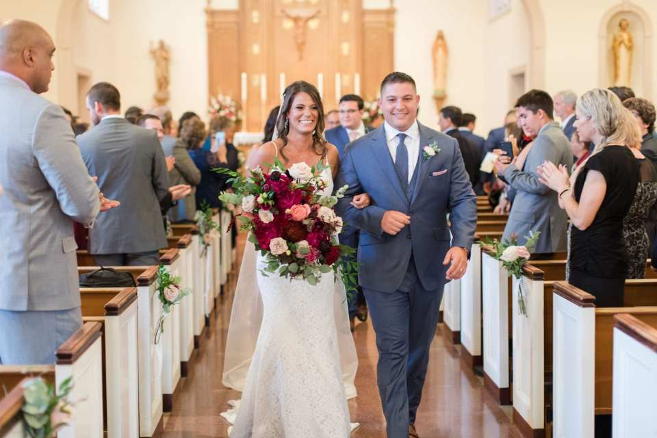 the bride and groom make their way back down the aisle of the church after being announced as husband and wife