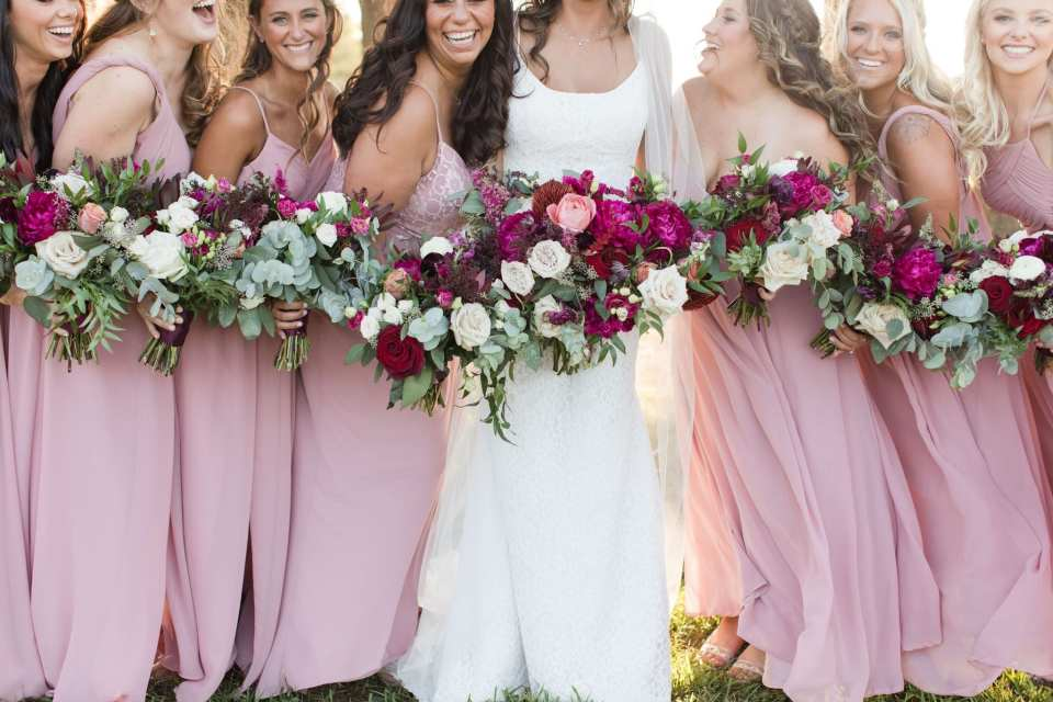informal 3/4 shot of the bride in her Mikaella gown with her bridal party in different styles of pink Azazie gowns and bouquets by Ivy on Main. Photography by Jaye Kogut Photography