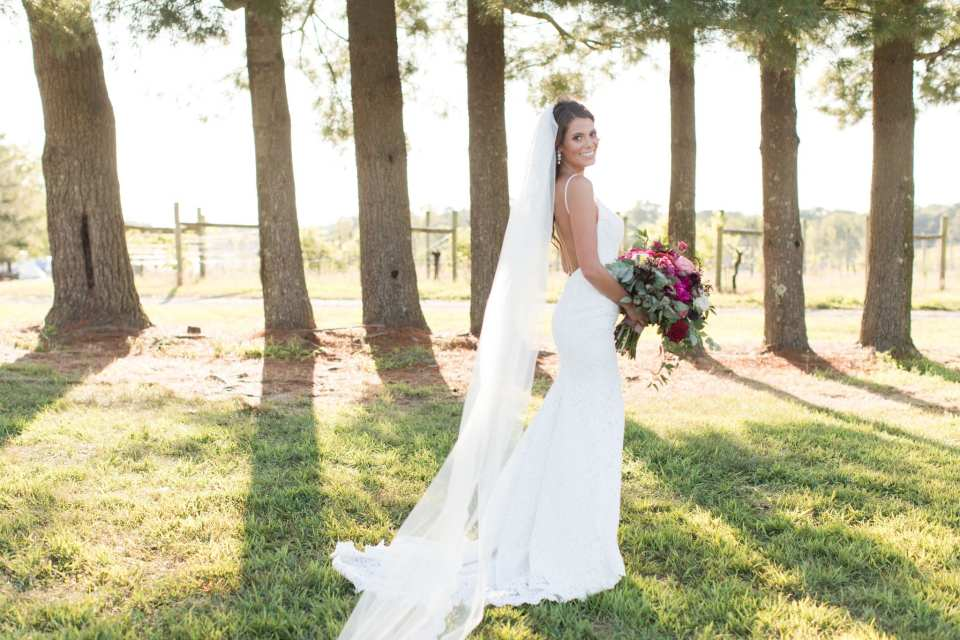 bridal portrait of the bride outside on the vineyard property, standing at an angle away from the camera, looking back at the camera smiling to expose the back of her Mikaella gown, while holding her bridal bouquet by Ivy on Main