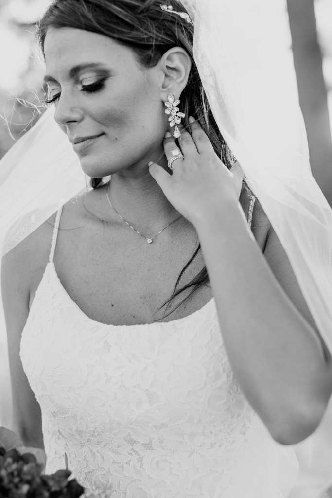 Black and white informal bridal portrait, with the brides eyes closed, her left hand brushing away her hair from her face