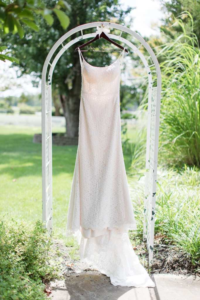 Bridal gown by Mikaella hangs on a white arch outdoors amongst trees and bushes at Laurita Winery