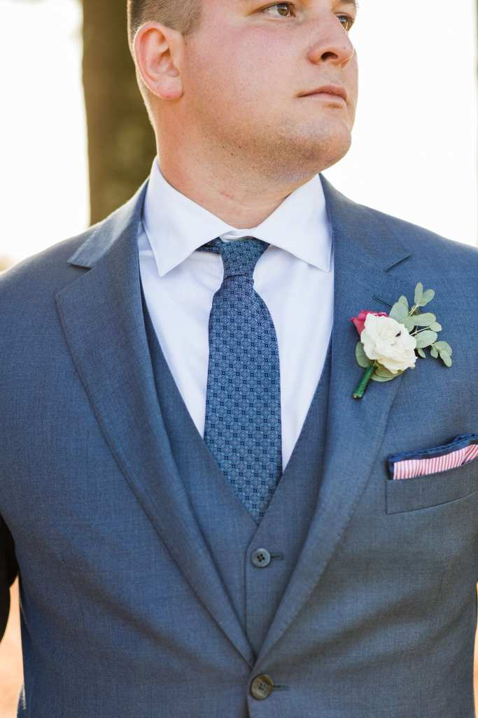 formal portrait of the groom looking serious in a blue suit by Generation Tux
