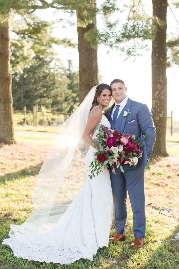 Formal portrait of the bride and groom outdoors, bride holding her bouquet of various florals in shades of dark pink, burgundy and cream by Ivy on Main