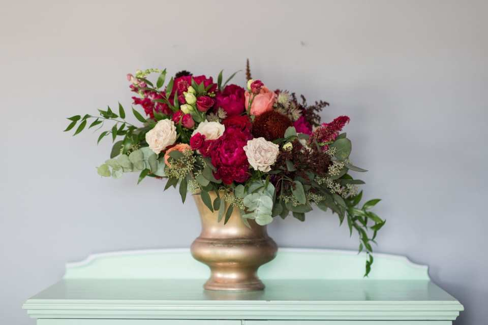 Florals in shades of dark pink, light pink, burgundy and greens in a gold urn by Ivy on Main