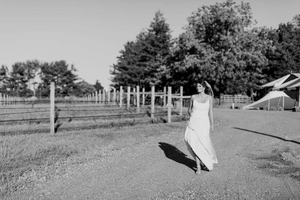 Black and white candid photo of the bride walking around the vineyard at Laurita Winery