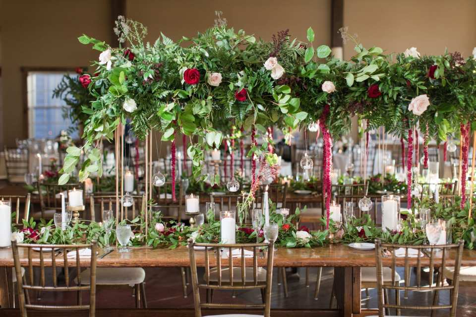 long wooden tables in the reception area with chivari chairs with tall arrangements the length of the table consisting of greens, accented with red, pink, white and burgundy flowers, with candles underneath by Ivy on Main