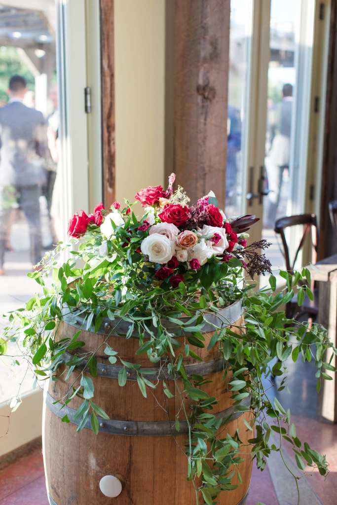 floral details on top of a wine barrely by Ivy on Main consisting of greenery with red, white and pink flowers