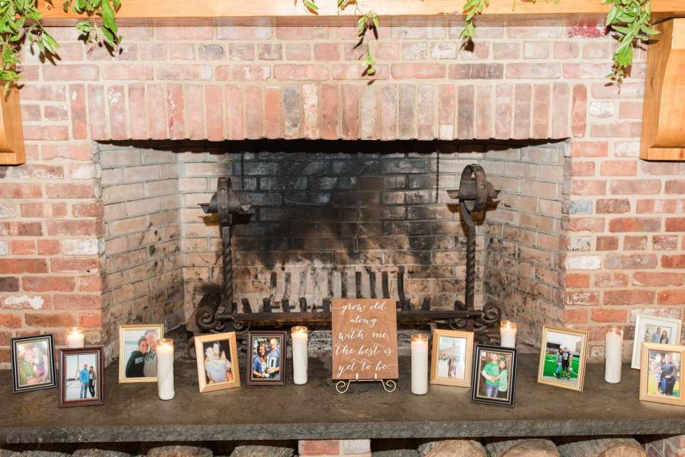 Display of photos of the newly married couple in front of a brick fireplace