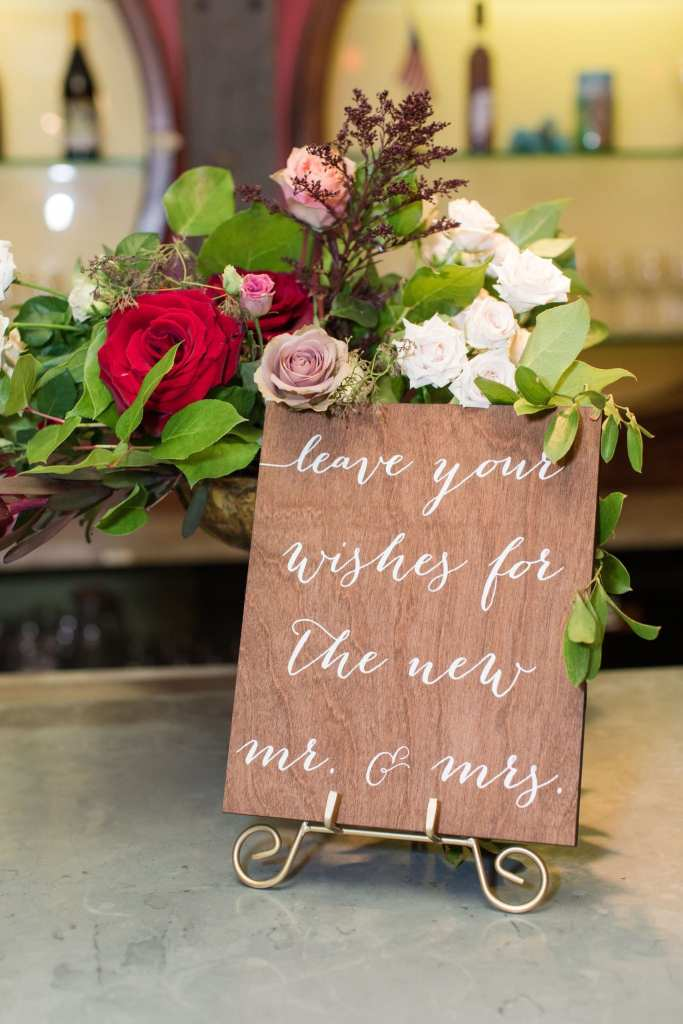 Detail photo of wooden signage for the guest book, with red, pink and white floral accents by Ivy on Main