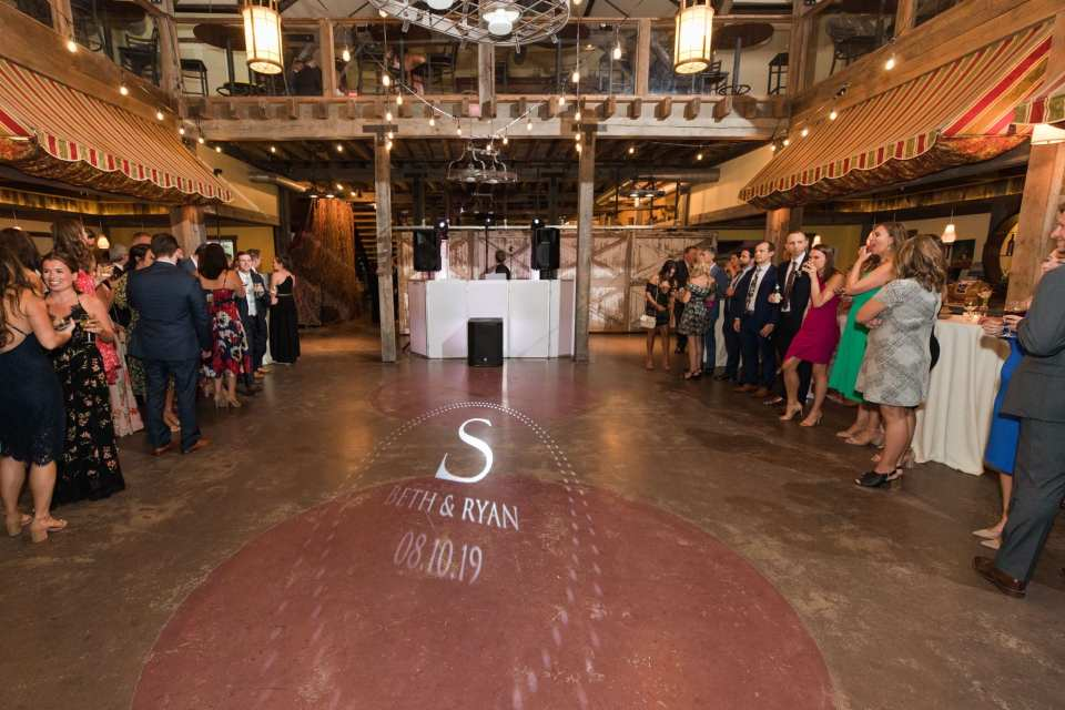 Wide shot of the Laurita Winery reception area, custom lighting on floor, guests waiting on either side of the room for the entrance of the bride and groom