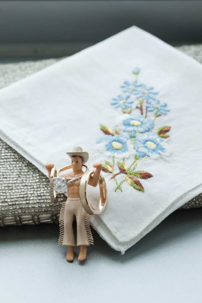 Wedding details photo of an embroidered handkerchief with a toy cowboy holding the engagement ring and wedding bands of gold on its arms