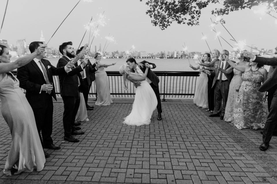 Black and white of the groom dipping his bride outside of the W Hotel Hoboken at dusk under and arch of sparklers, with the New York City skyline in the background