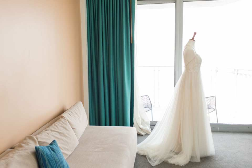 The wedding gown from the side, displayed on a bust in front of the floor length windows inside the W Hotel Hoboken