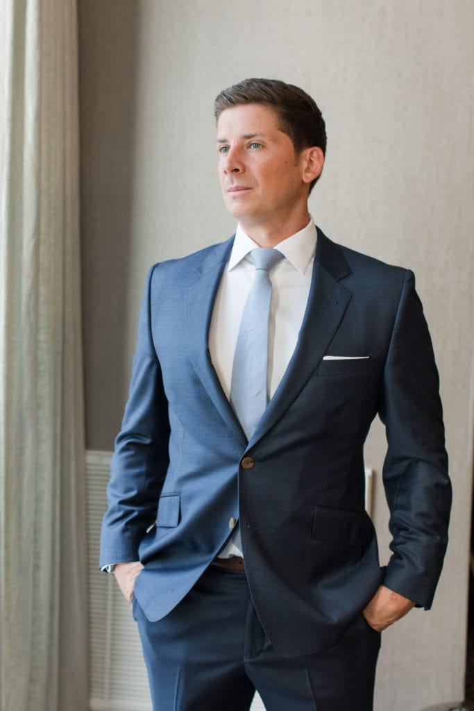 Formal photo of the groom in his dark blue suit with light blue tie
