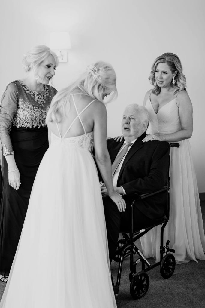 Black and white candid photo of the bride with her father, as her sister and mother look on
