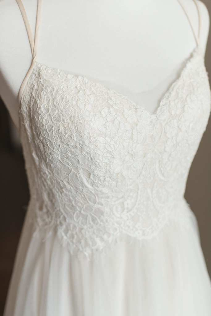 Close up of the lace detail on the bodice of the wedding gown while its on a white bust