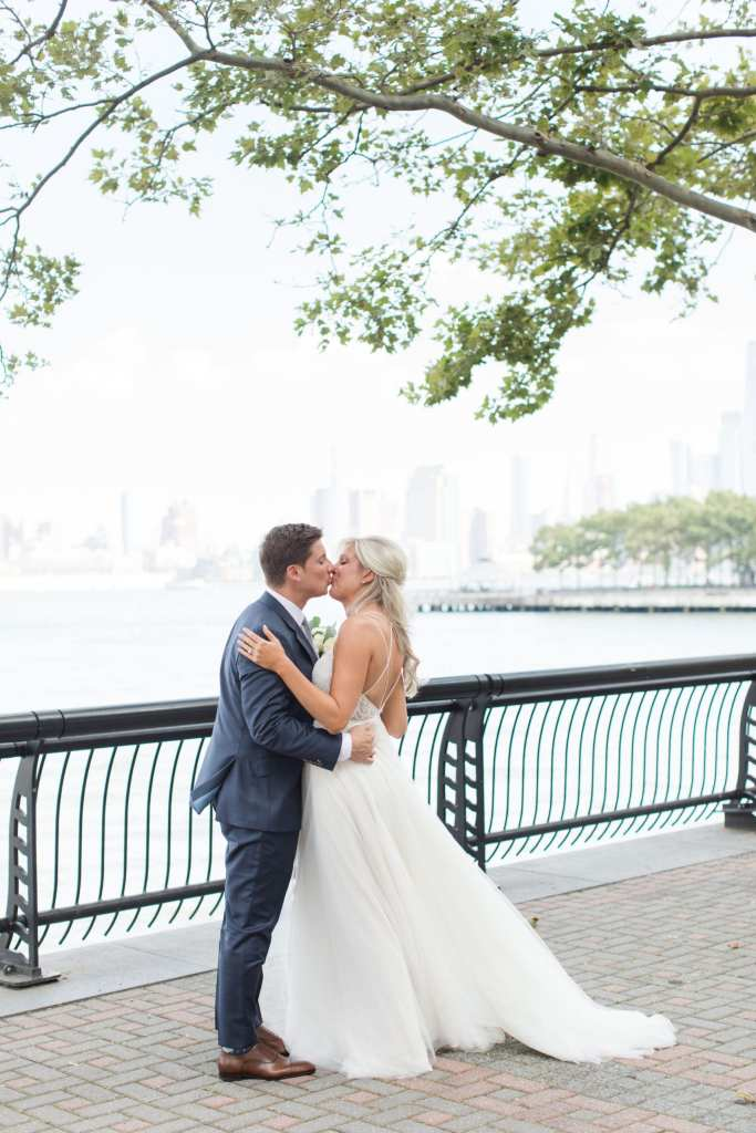 The bride and groom kiss during their first look on the waterfront outside the W Hotel Hoboken with the New York City skyline in the distance