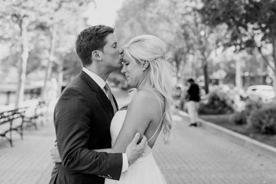 Black and white candid photo of the bride and groom in each others arms, the groom kissing the brides forehead