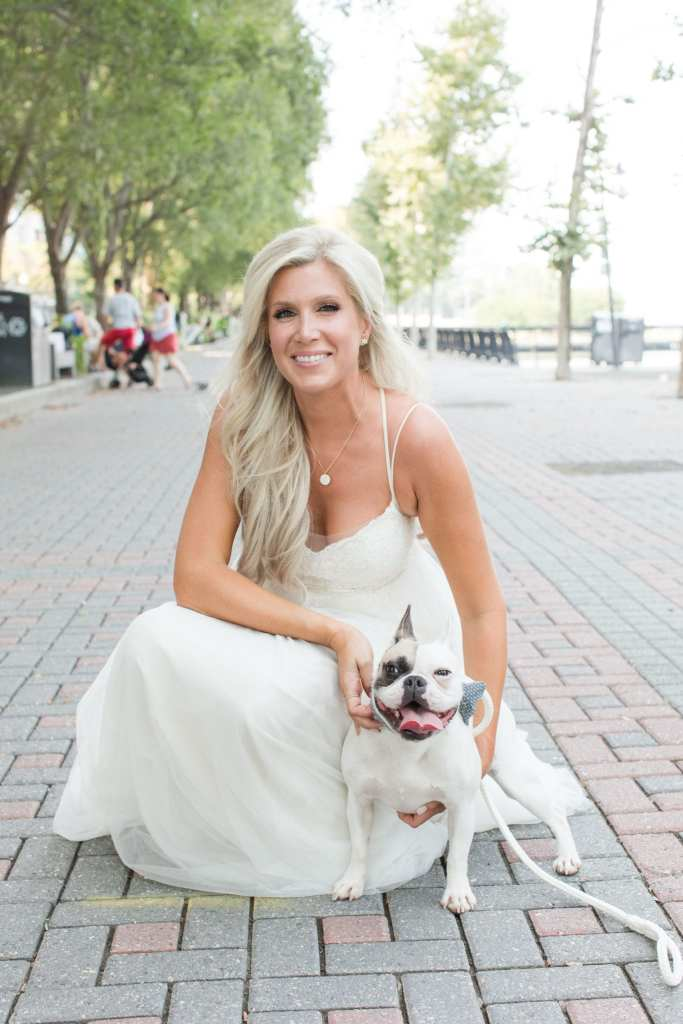 Bride crouching down to the ground holding her dog outside in Hoboken