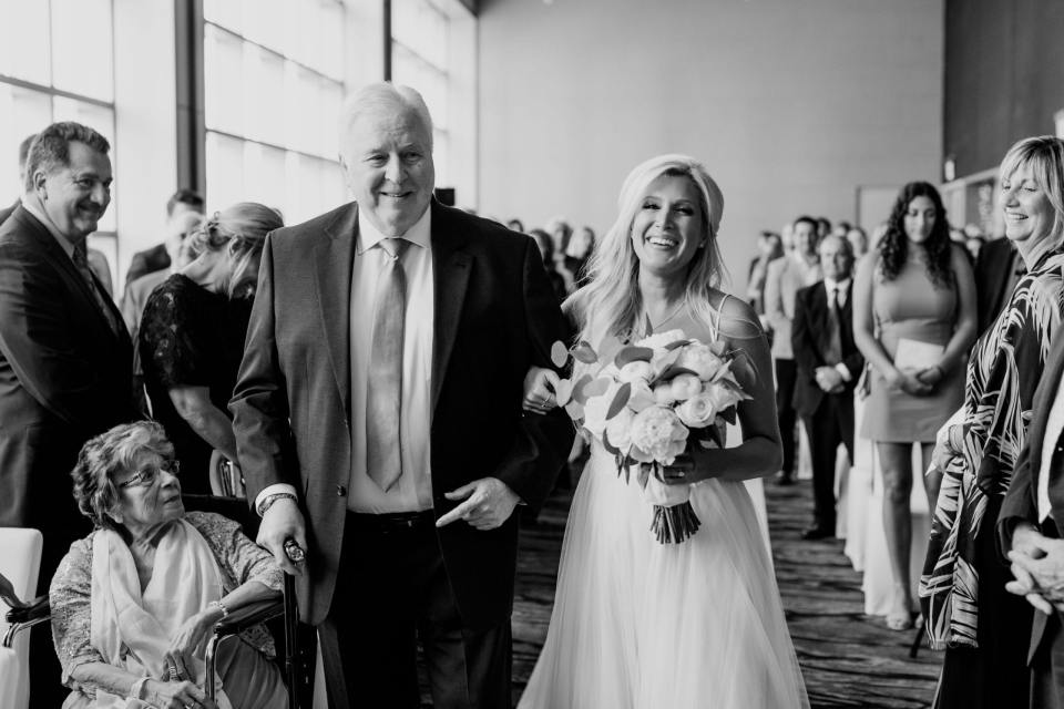 Black and white photo of the bride being walked down the aisle by her father