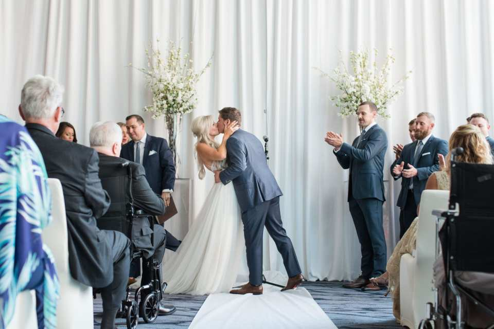 The bride and groom share their first kiss as husband and wife in front of wall draped in white fabric with tall white floral arrangements on either side of them