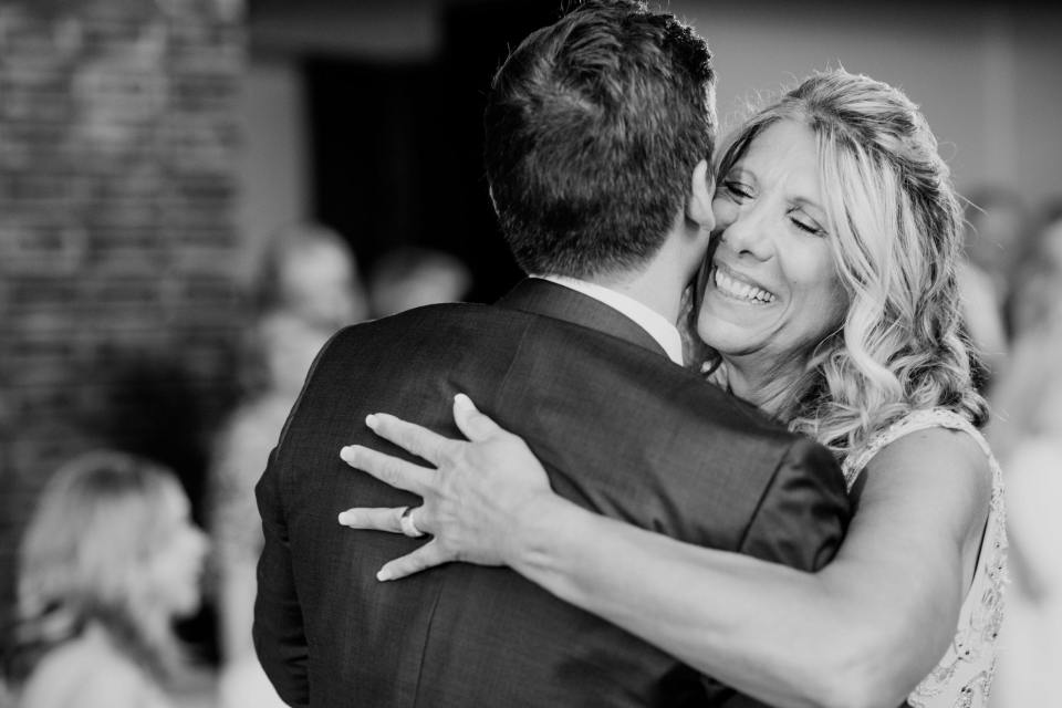 Black and white close up of the mother of the grooms face while she dances with her son