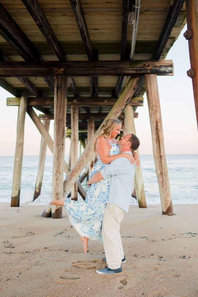 Classic couple shot where he is lifting her up in the air, her arms wrapped around his neck.under the boardwalk at Jenkinson's Beach by New Jersey wedding photographer