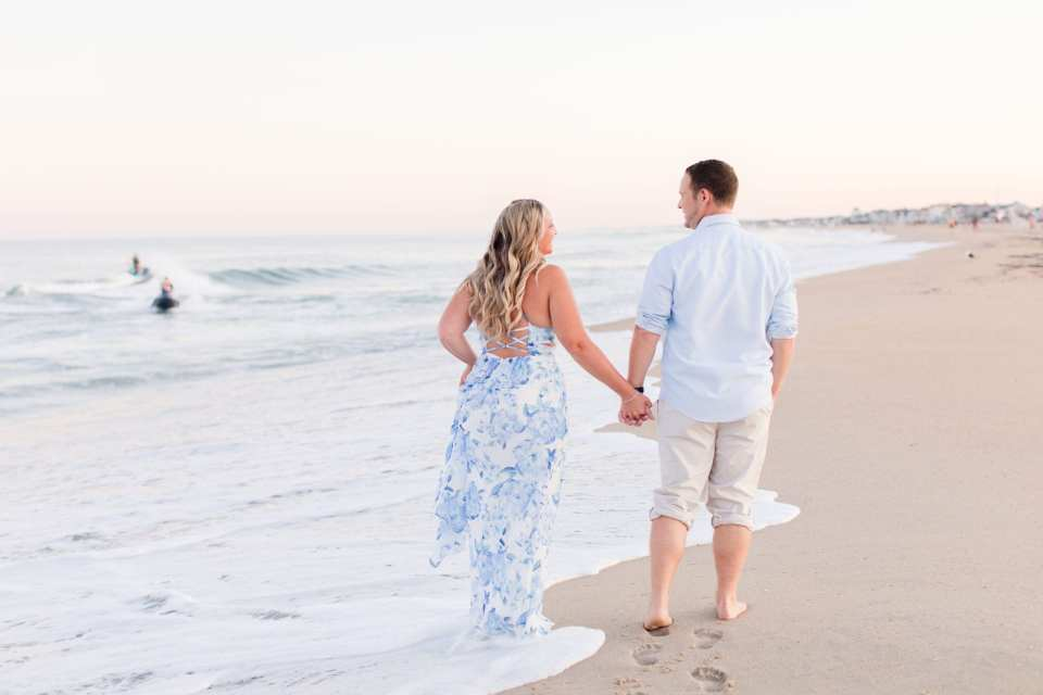 Bride to be in a blue patterned maxi dress by Morgan and Co. from Macy's, groom to be in a classic blue oxford button down and rolled up khaki pants walking hand in hand on the beach, away from camera, at Jenkinson's Beach by NJ wedding photographer Jaye Kogut Photography