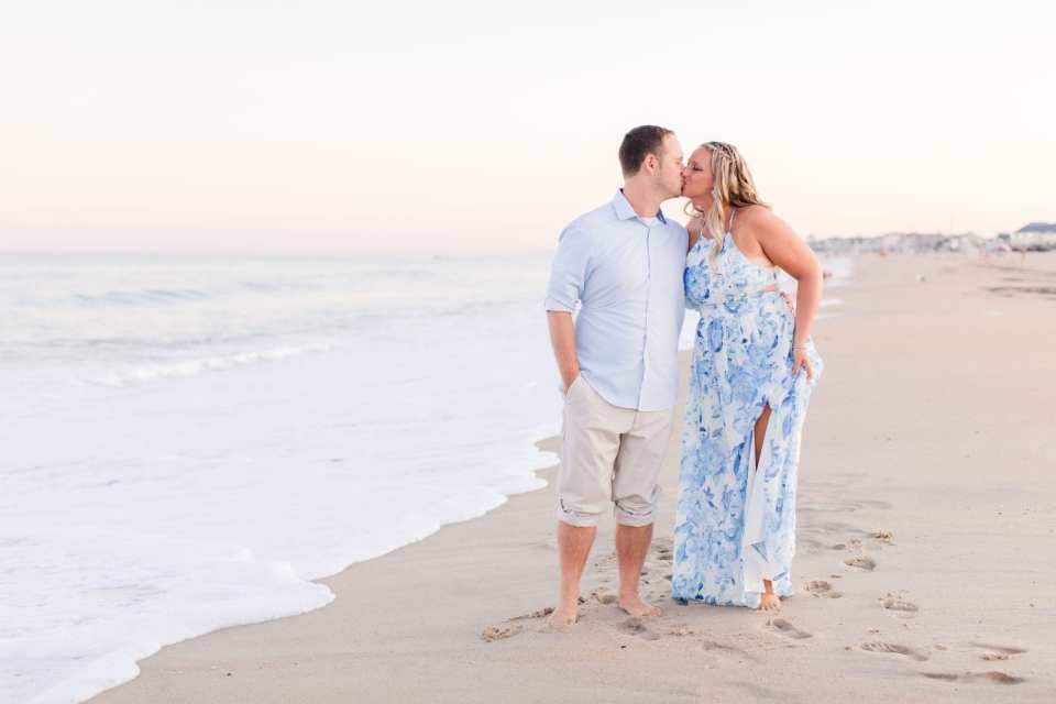 Groom to be in classic blue oxford shirt and rolled up khaki pants, kissing his bride to be, whom is in a blue and white print maxi dress, on the beach