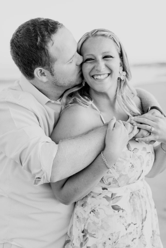 black and white photo of man encircling woman in his arms, while she is looking towards the camera laughing and he is kissing her cheek