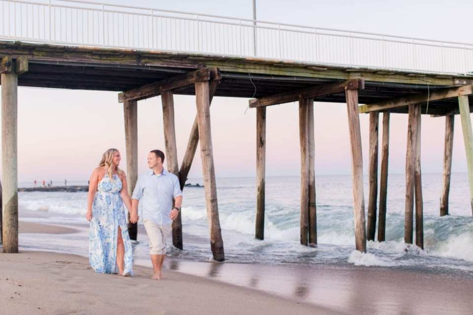 Bride to be in a blue patterned maxi dress by Morgan and Co. from Macy's, groom to be in a classic blue oxford button down and rolled up khaki pants walking hand in hand on the beach in front of the boardwalk at Jenkinson's Beach by NJ wedding photographer Jaye Kogut Photography