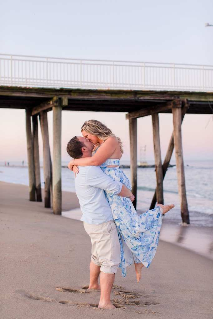 Classic couple shot where he is lifting her up in the air, her arms wrapped around his neck, kissing each other. On the beach in front of the boardwalk at Jenkinson's Beach by New Jersey wedding photographer