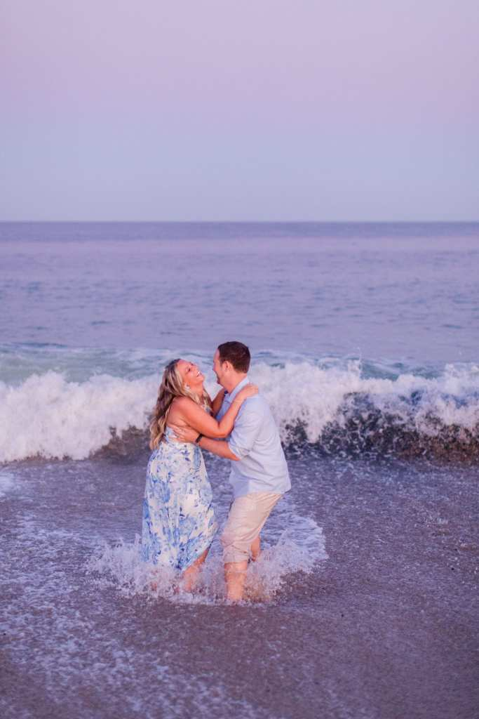 Engaged couple laughing with one another, while holding each other, in the waves at Jenkinson's Beach by NJ engagement photographer