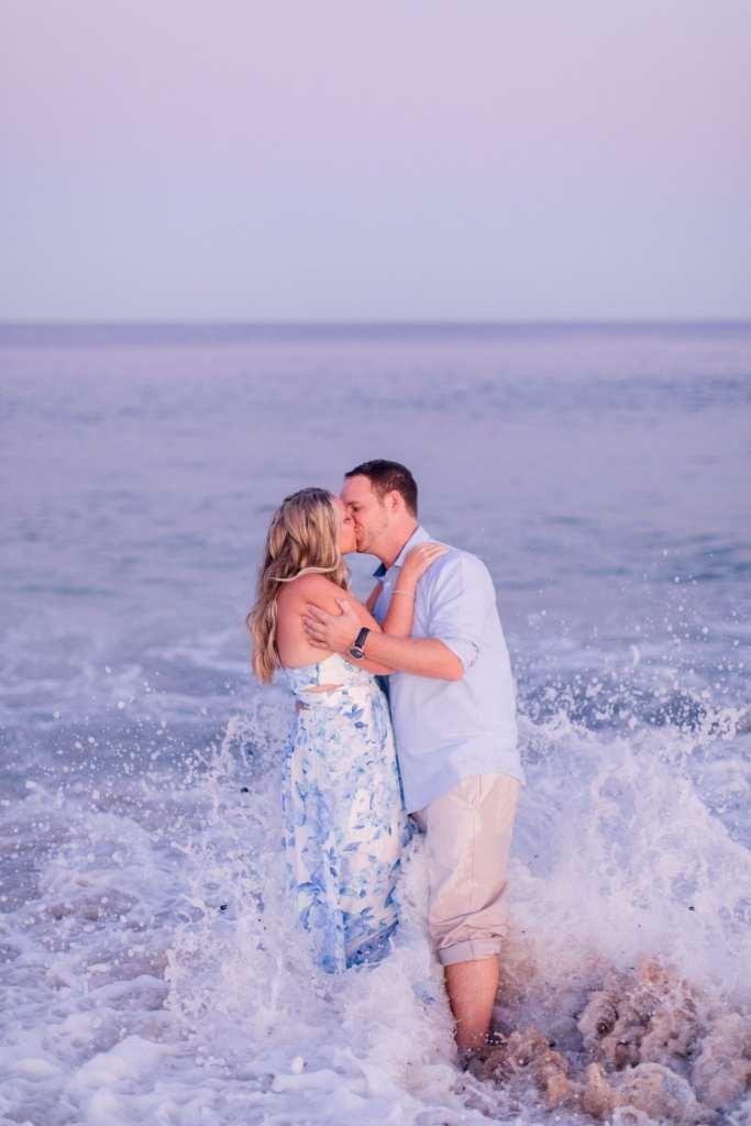 Engaged couple kissing, while holding each other, in the waves at Jenkinson's Beach by NJ engagement photographer