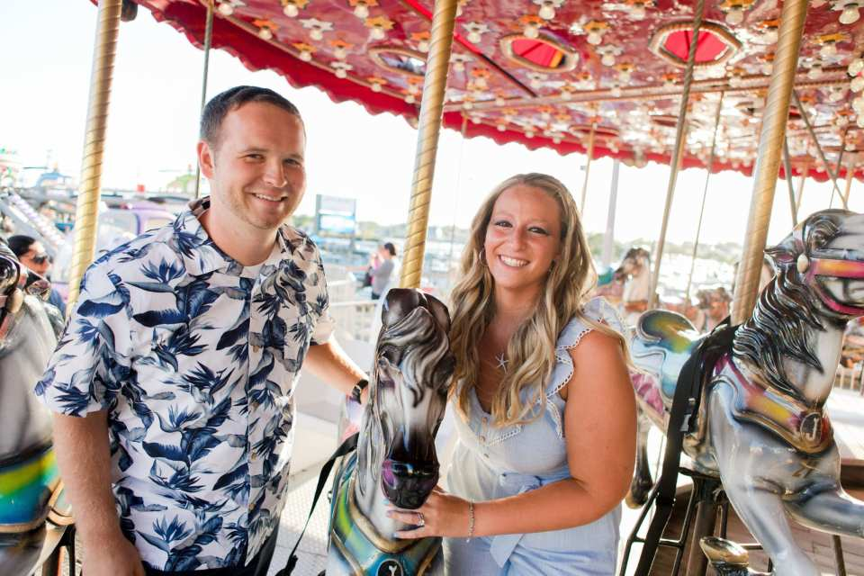 engaged couple ride the carousel together on Jenkinson's Pavilion. She is wearing a starfish necklace from Sunshine Daydream