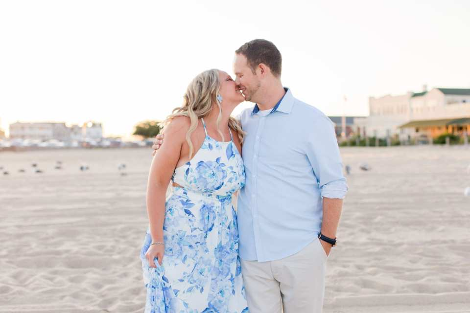 bride and groom to be kissing on the beach