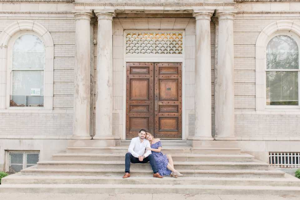 Bride and groom to be sitting on the steps of a historic building at the Philadelphia Navy Yard  in Philadelphia, PA by NJ wedding photographer Jaye Kogut Photography