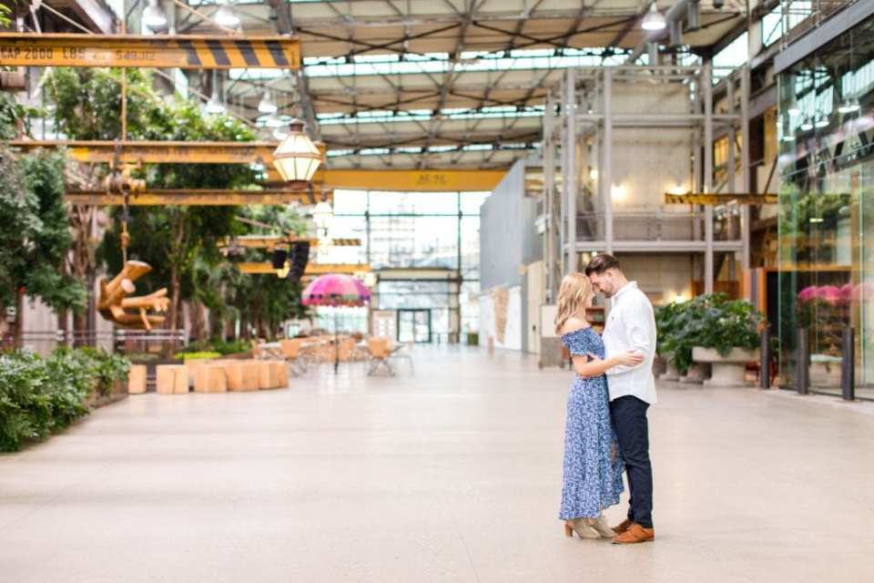 Engaged couple standing facing each other, forehead to forehead, arm in arm, inside a building filled with plants in Philadelphia, PA by NJ wedding photographer