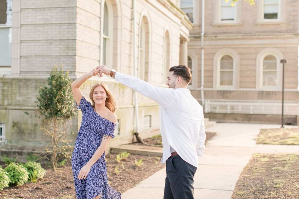 Groom to be twirling his bride to be in front of historic buildings at Philadelphia Navy Yard  in Philadelphia, PA
