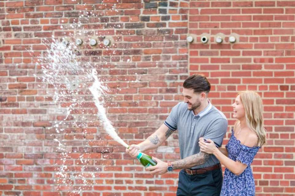 Groom to be popping a bottle of bubbly with his bride to be smiling with glee slightly behind him, in front of a brick wall at the Philadelphia Navy Yard