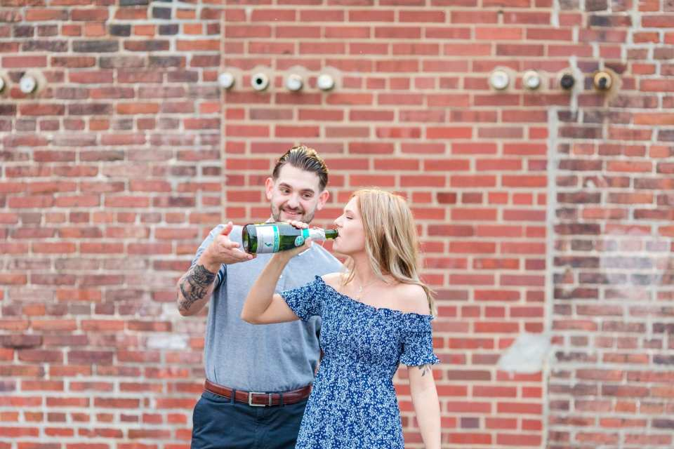 Bride to be drinking from a bottle of bubbly, being helped by her groom to be, in front of a brick wall at the Philadelphia Navy Yard