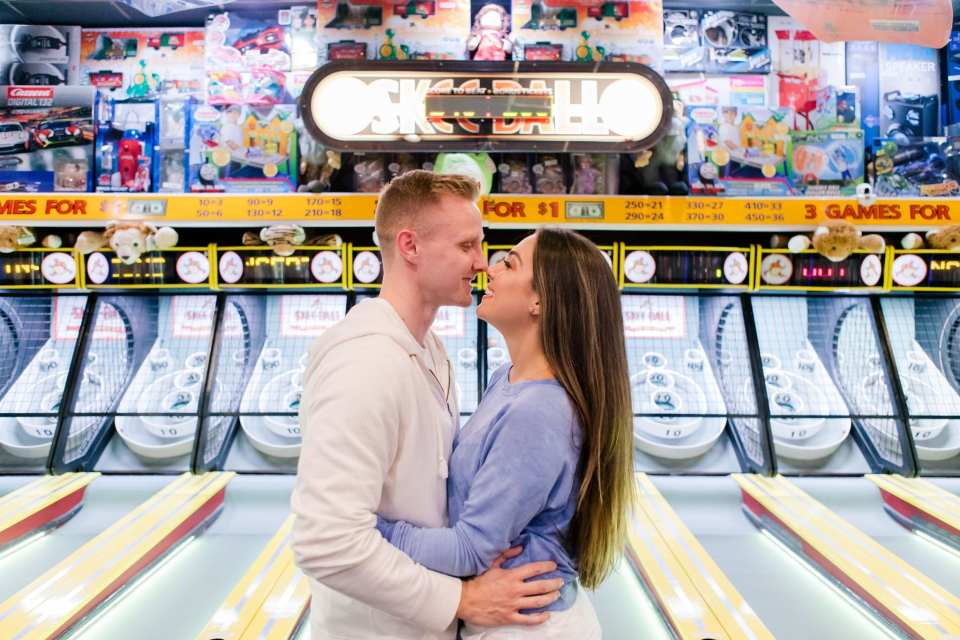 Casual and fun shot of the couple in one anothers arms in front of the skeeball machines on Jenkinson's Pavilion