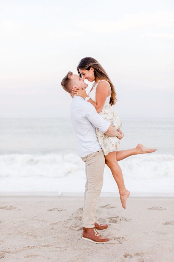 Classic couple shot where he is lifting her up in the air, her arms wrapped around his neck, nose to nose. On the beach by New Jersey wedding photographer