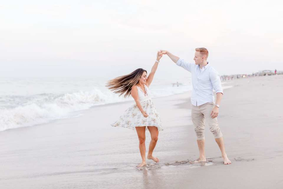 Groom to be dancing and twirling his bride to be on the beach, waves crashing in the background in Point Pleasant, NJ by Jaye Kogut Photography