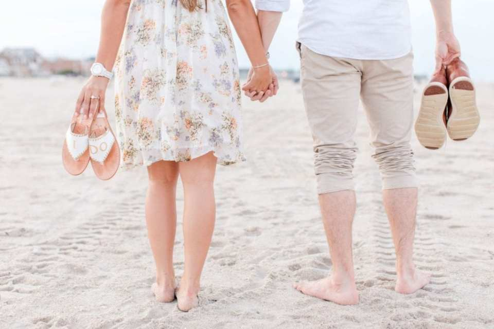 "lower half of body photo walking on beach, hand in hand, with the brides sandals saying ""i do"""