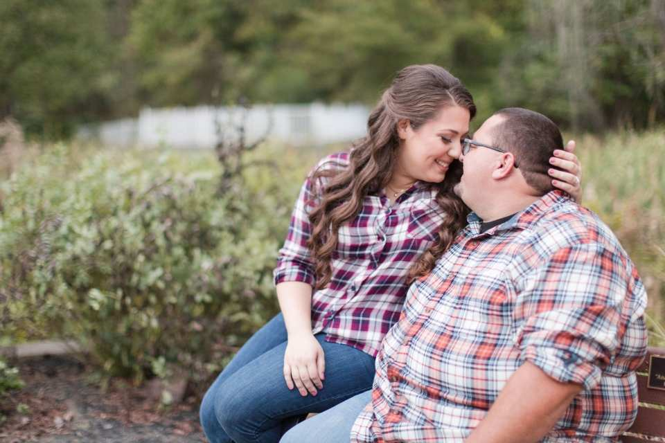 Engaged couple in flannel shirts nose to nose on a bench, sayen gardens engagement photos