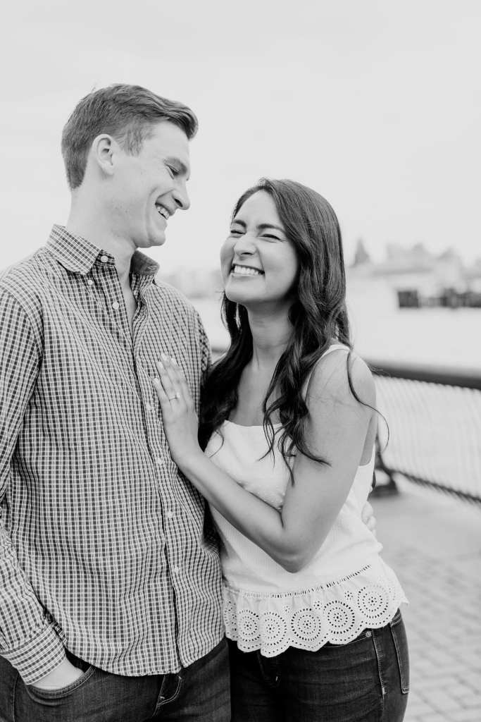 Black and white fun photo of the couple laughing; her left hand on his chest displaying her engagement ring