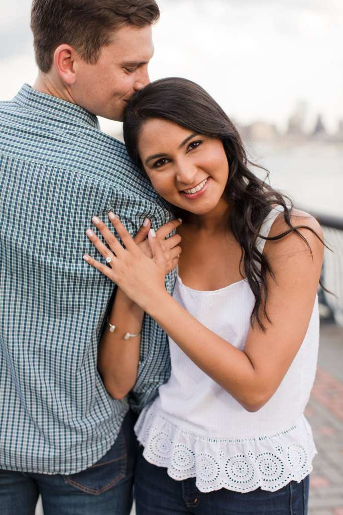 Groom to be facing away from the camera, while she is wrapped around his right arm, facing the camera, head on his shoulder, her round diamond solitaire engagement ring on display on the back of his shoulder. Her top by J. Crew